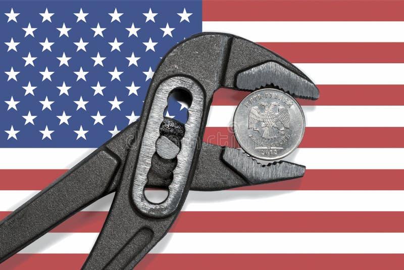 La pièce de monnaie dans l'étau sur le fond du drapeau des Etats-Unis photo libre de droits