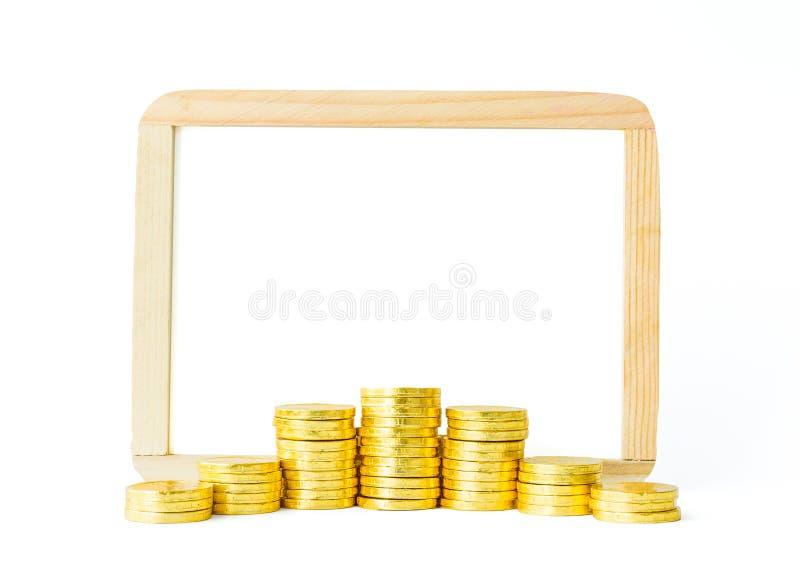 La pièce de monnaie et le tableau blanc d'or avec le blanc ont isolé le fond, qui photos stock