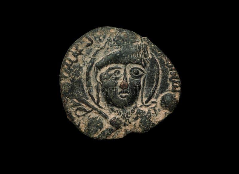 La pièce de monnaie islamique de cuivre antique avec le visage là-dessus a isolé sur le noir image libre de droits