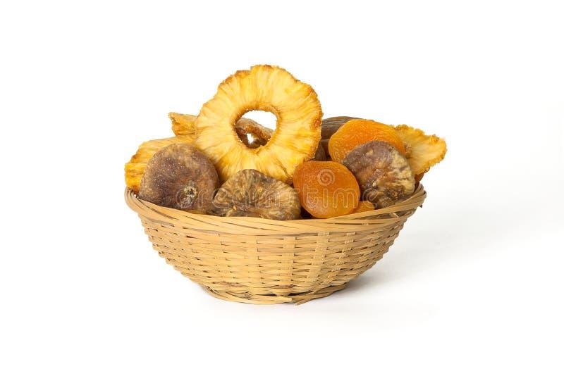 La piña, los albaricoques y los higos secados en una cesta de mimbre aislaron o imágenes de archivo libres de regalías