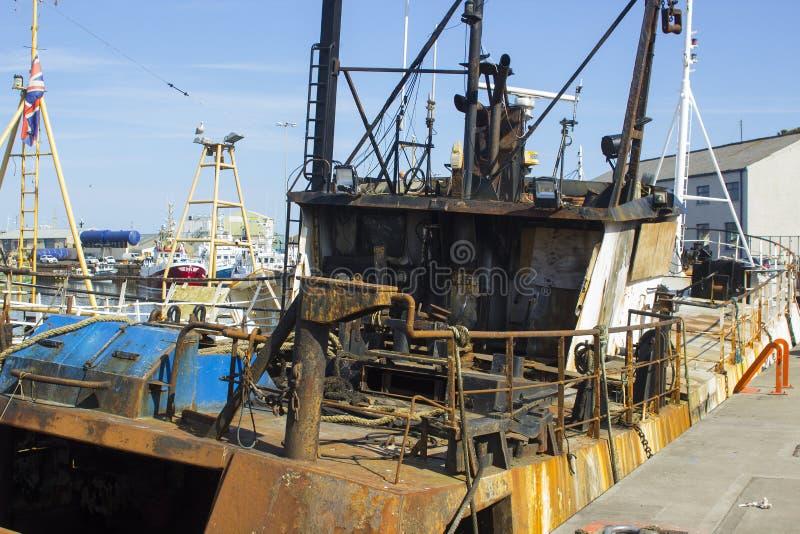 La piattaforma di una sciabica danneggiata dall'incendio ha ancorato alla banchina nel porto Irlanda del Nord di Kilkeel fotografia stock