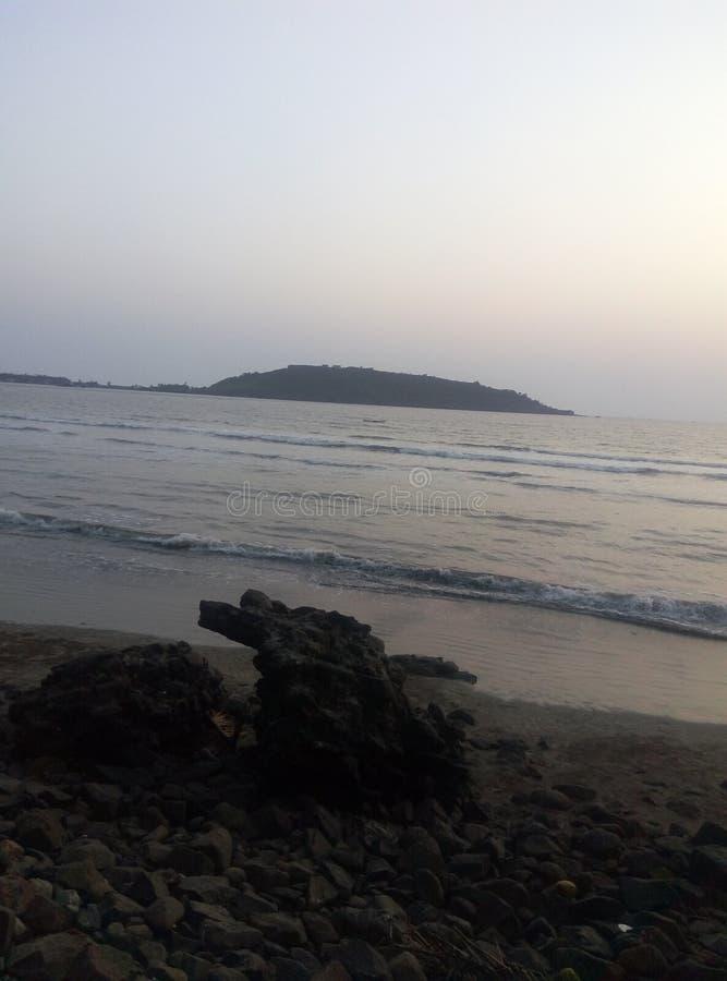La PIC de l'eau de mer lentement en mouvement et d'une partie de terre avec quelques pierres photographie stock