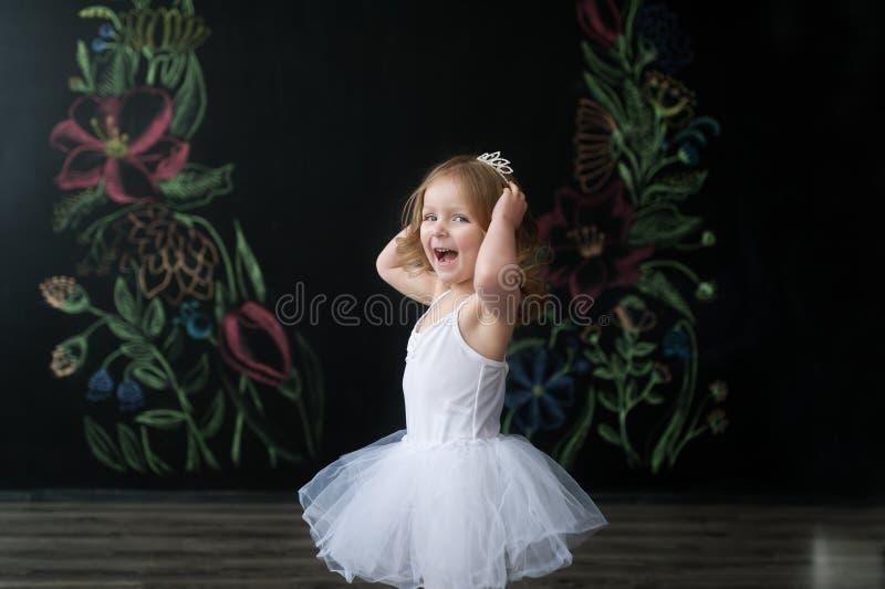 La piccola ballerina sveglia in costume bianco di balletto sta ballando nella stanza Bambino nella classe di ballo immagini stock libere da diritti