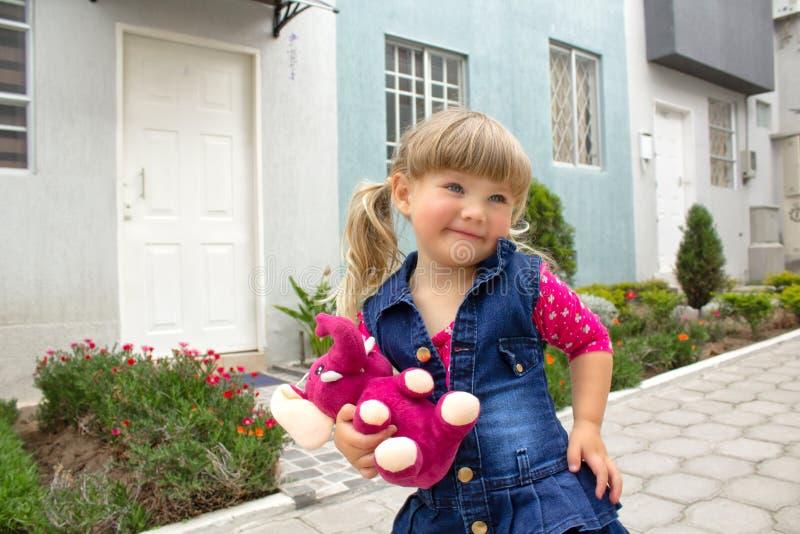 La piccola bella ragazza cammina con un giocattolo molle in loro mani su aria aperta immagine stock libera da diritti