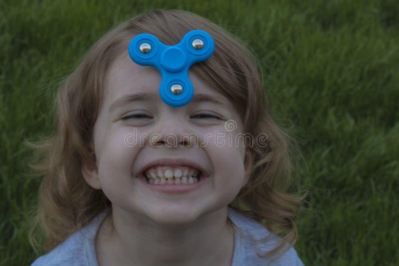 La piccola bella ragazza del ritratto sta giocando il filatore blu immagini stock