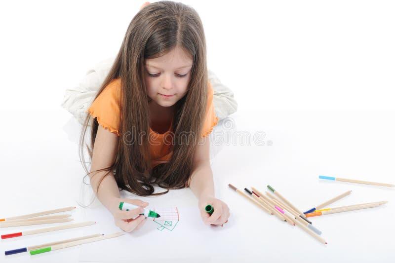 La piccola bella ragazza estrae le matite. fotografia stock