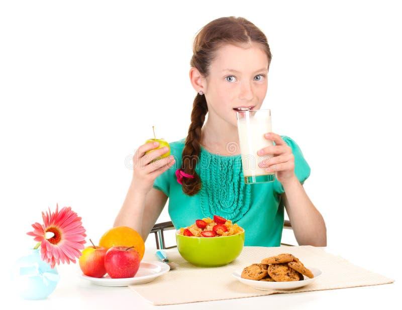 La piccola bella ragazza ha una prima colazione fotografia stock