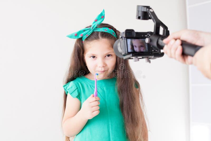 La piccola bella ragazza pulisce l'odontoiatria dello spazzolino da denti dei denti fotografia stock