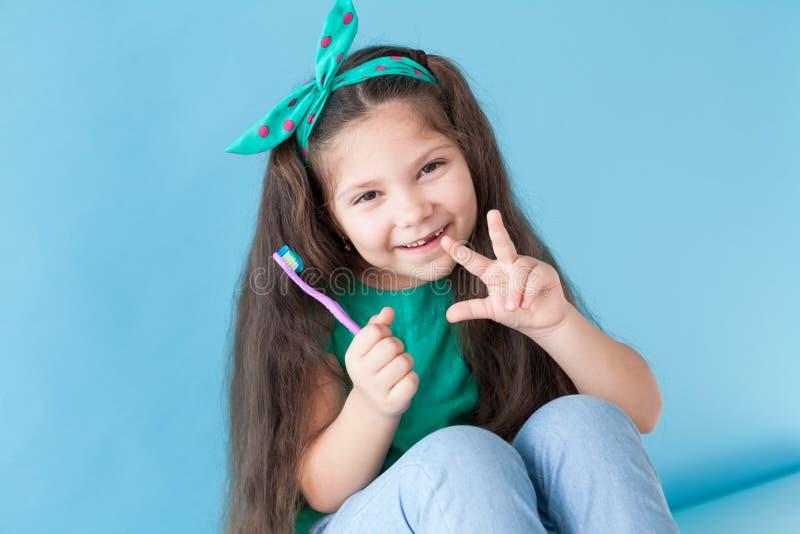 La piccola bella ragazza pulisce l'odontoiatria dello spazzolino da denti dei denti immagine stock