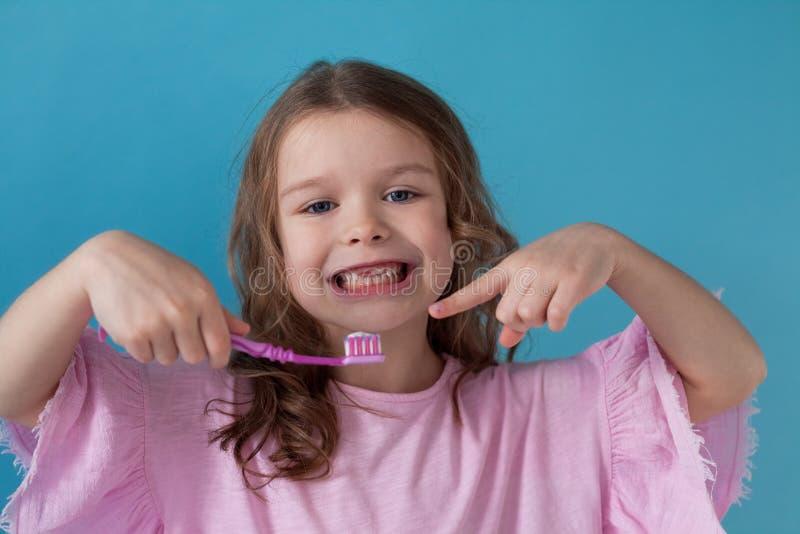 La piccola bella ragazza pulisce l'odontoiatria dello spazzolino da denti dei denti fotografia stock libera da diritti