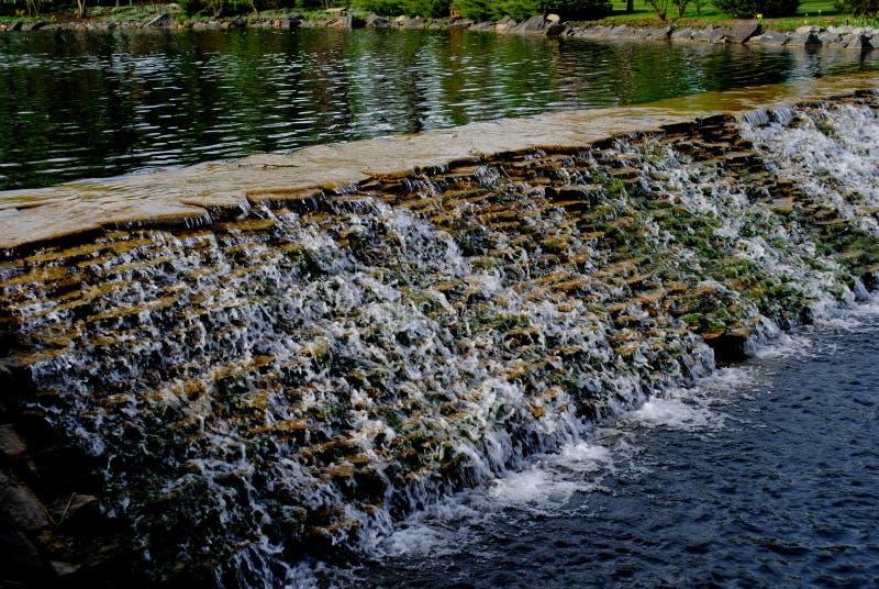 La piccola cascata artificiale nel parco fotografia stock