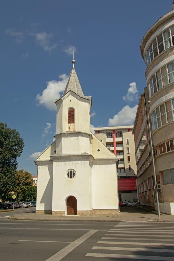 La piccola chiesa evangelica modesta dentro betzeen le costruzioni di appartamento moderne Alba Iulia, Romania fotografia stock libera da diritti