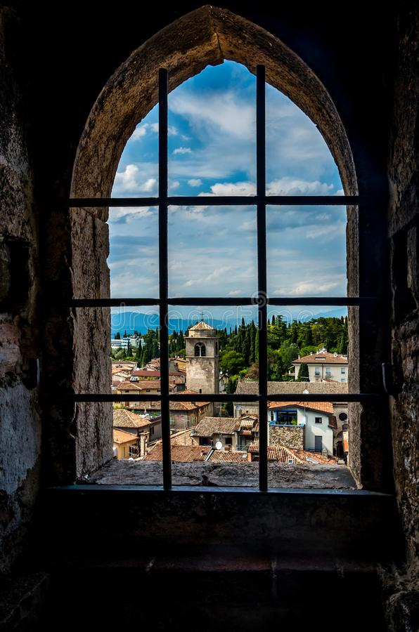 La piccola città pittoresca Sirmione dalla polizia del lago in Italia ha incorniciato in una finestra immagini stock libere da diritti