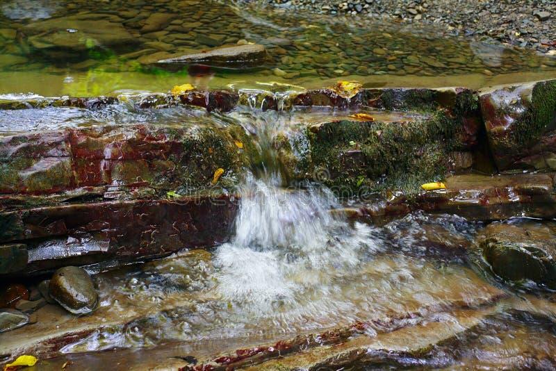 La piccola corrente tranquilla dell'insenatura della montagna scorre fra le rocce fotografia stock libera da diritti