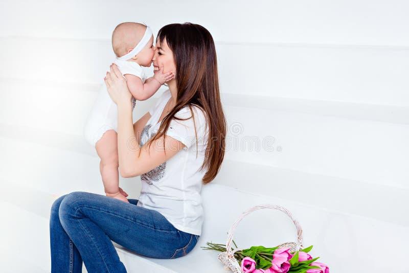 La piccola figlia sorridente del bambino morde la sua mamma del naso castana in briciolo fotografia stock libera da diritti