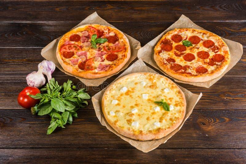 La piccola mini pizza mini, miniatura sulla carta di cottura su un buio corteggia immagini stock