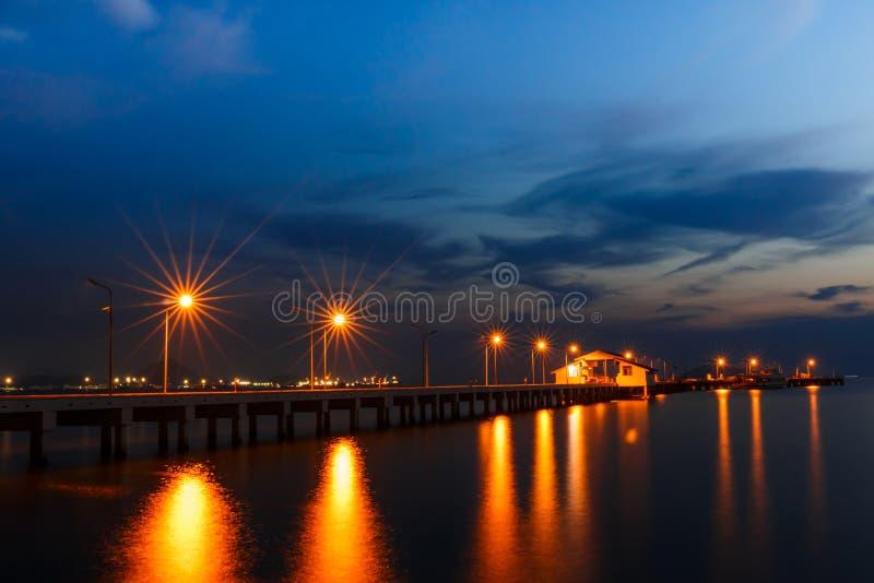 La piccola nave del porto e riflette la lampada nella notte fotografie stock