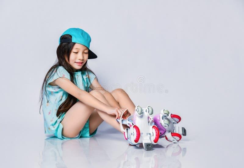 La piccola neonata asiatica sorridente in cappuccio fresco del cappello si siede sul pavimento e mette sui pattini di rullo su bi fotografie stock libere da diritti