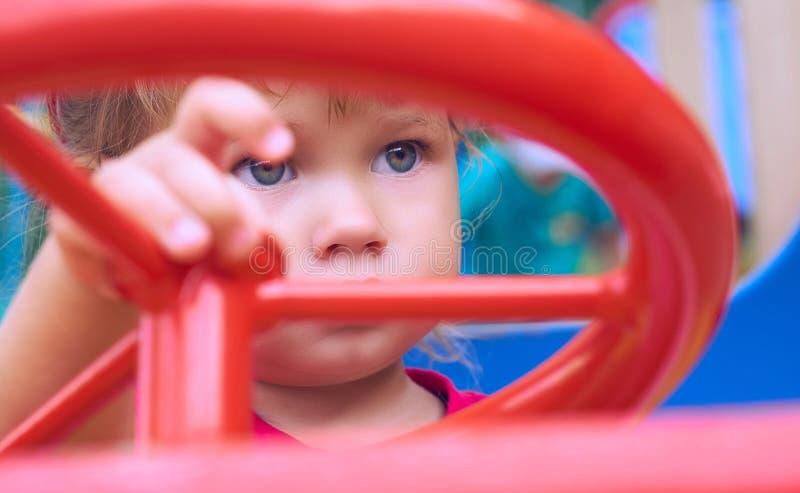 La piccola neonata caucasica si siede alla ruota di un'automobile del giocattolo Giocando sul concetto del campo da giuoco fotografia stock libera da diritti