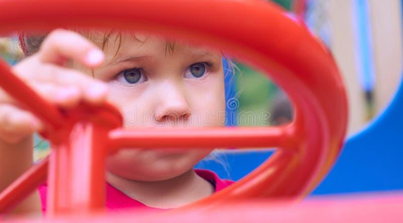 La piccola neonata caucasica si siede alla ruota di un'automobile del giocattolo Giocando sul concetto del campo da giuoco immagine stock libera da diritti