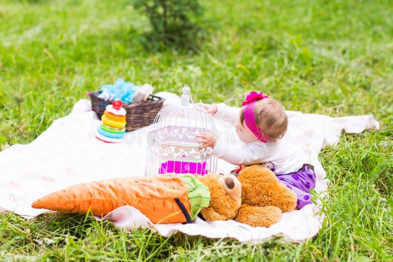 La piccola neonata felice sveglia con il grande orsacchiotto marrone riguarda il prato, la molla o la stagione estiva dell'erba v immagini stock