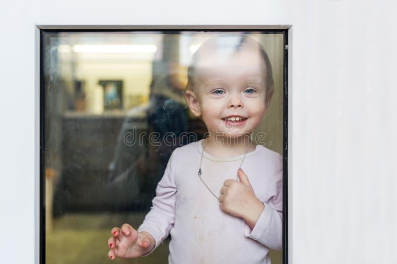 La piccola neonata ha premuto il suo naso alla finestra domestica fotografia stock libera da diritti