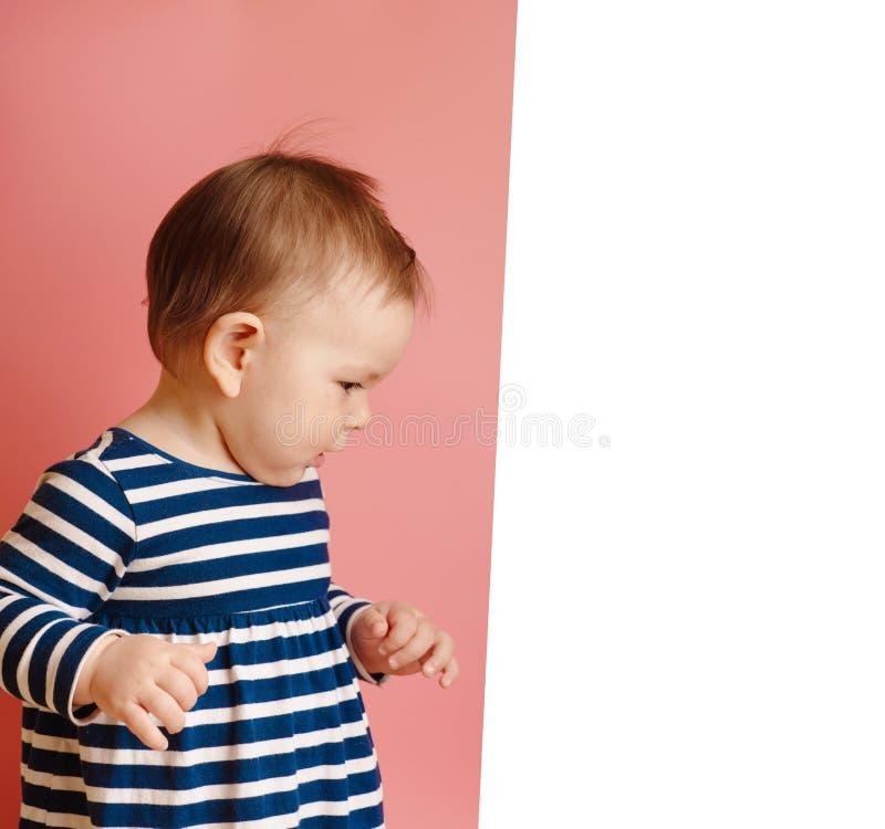 La piccola neonata leggiadramente adorabile si sente bene e sorride sul rosa immagine stock libera da diritti