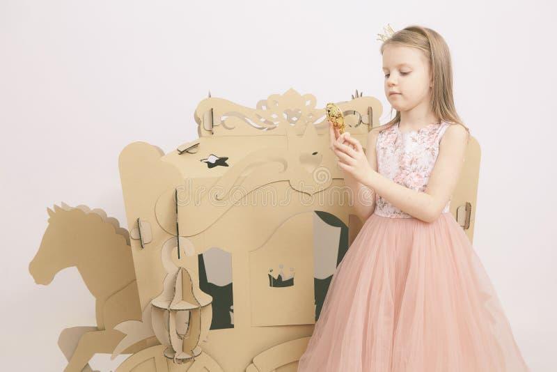 La piccola principessa guarda nello specchio Specchio della tenuta della bambina Modo e bellezza, infanzia Ragazza del bambino in immagine stock