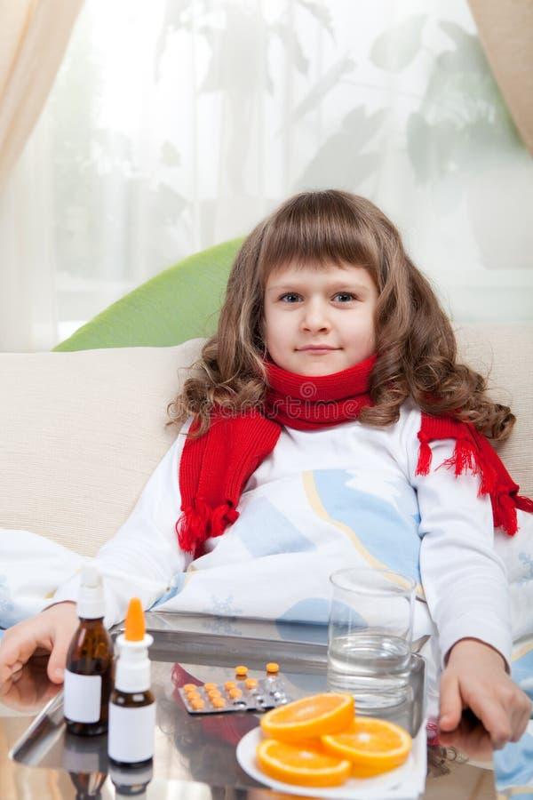 La piccola ragazza ammalata in base sta catturando la medicina fotografia stock