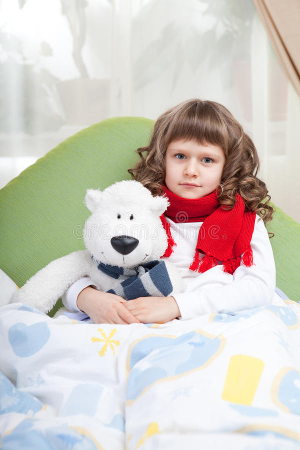 La piccola ragazza ammalata con la sciarpa abbraccia l'orso del giocattolo immagine stock