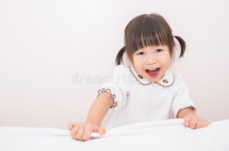 La piccola ragazza asiatica adorabile sveglia nel suo letto immagini stock libere da diritti