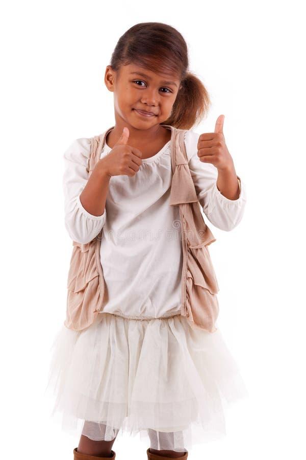 La piccola ragazza asiatica africana sveglia che fa i pollici aumenta il isolat di gesto immagini stock libere da diritti