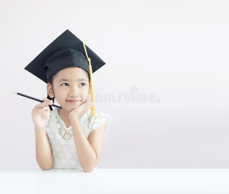 La piccola ragazza asiatica del ritratto sta indossando la matita laureata della tenuta del cappello che si siede pensando qualco fotografie stock libere da diritti