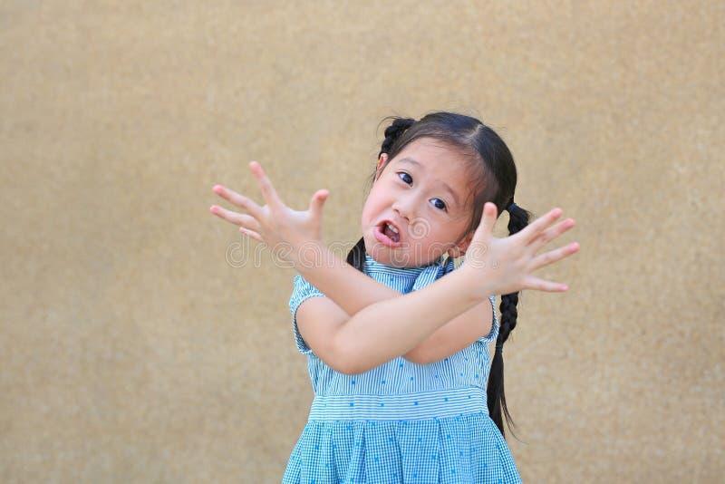 La piccola ragazza asiatica sfacciata del bambino con il fronte divertente e l'espressione attraversano il suo braccio immagini stock