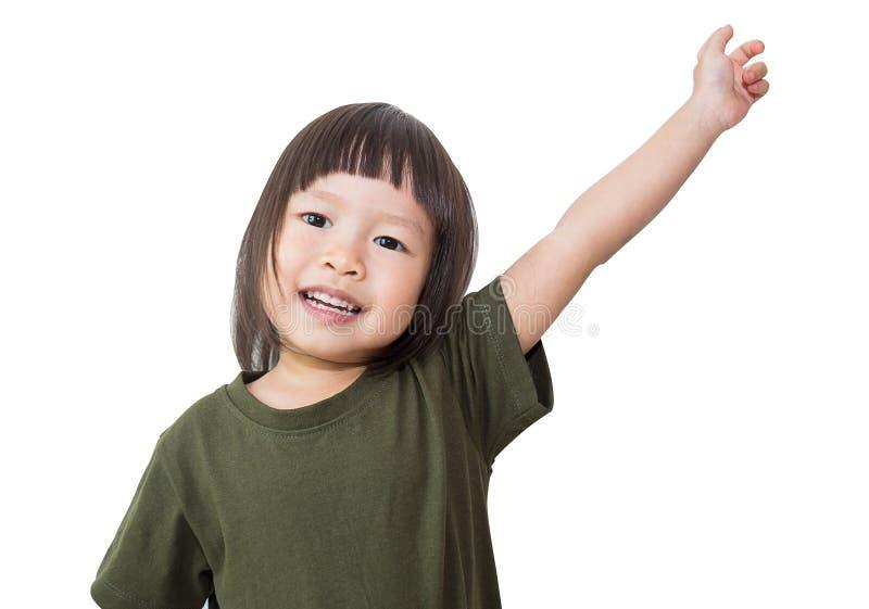 La piccola ragazza asiatica sveglia aumenta la sua mano su sopra fondo bianco fotografia stock libera da diritti