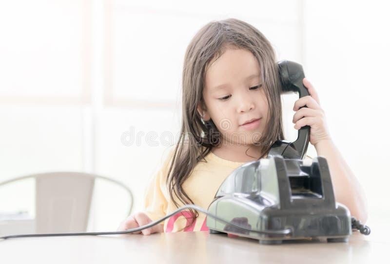 La piccola ragazza asiatica sveglia sostiene il vecchio telefono fotografia stock