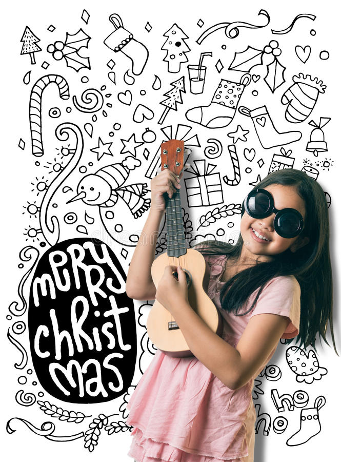La piccola ragazza asiatica sveglia sta giocando la chitarra circa il Natale immagini stock libere da diritti