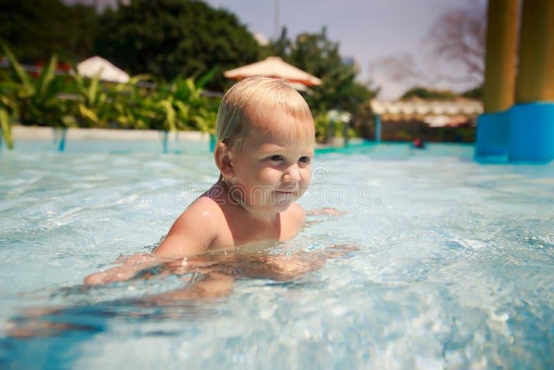 la piccola ragazza bionda bagna i giochi di sorrisi nella piscina dell'hotel fotografia stock libera da diritti