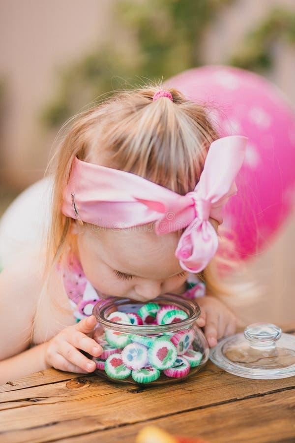 La piccola ragazza bionda con il foulard rosa sulla sua testa fiuta in una caramella variopinta del barattolo di vetro fotografia stock
