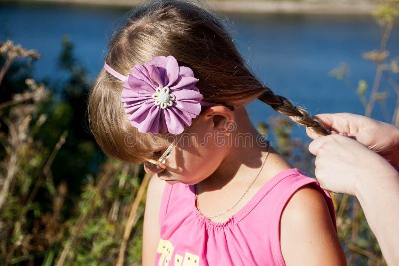 La piccola ragazza bionda di cui la madre intreccia immagini stock