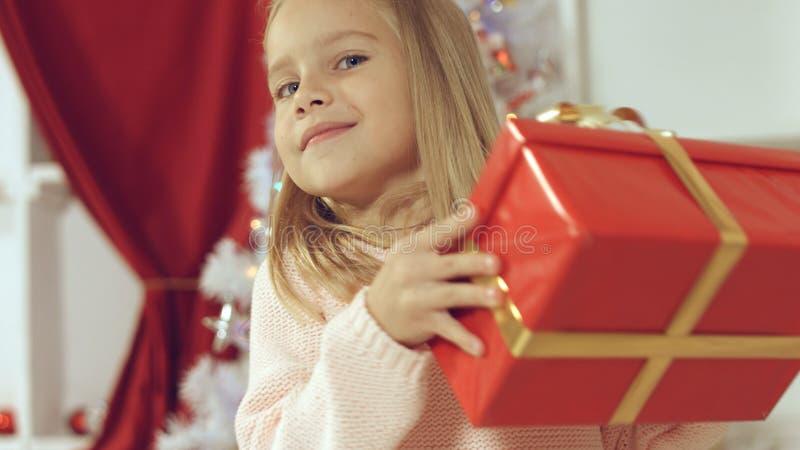 La piccola ragazza bionda favorita è contentissima dal suo regalo del ` s del nuovo anno fotografia stock