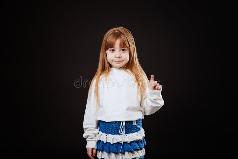 La piccola ragazza bionda seria con i vetri indica il dito il lato fotografia stock