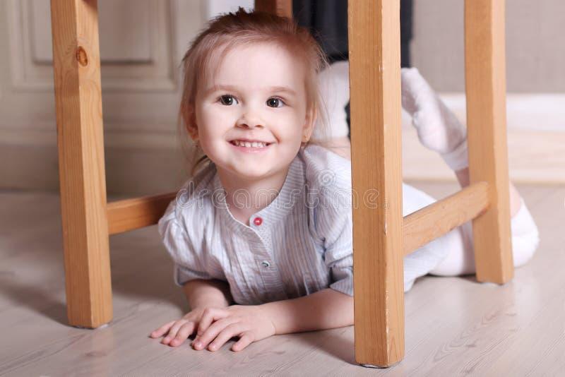 La piccola ragazza bionda sveglia in camicia a strisce sta sorridendo sul unde del pavimento immagini stock libere da diritti