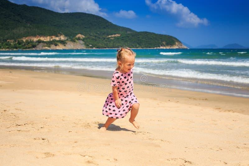 La piccola ragazza bionda in vestito chiazzato salta sulla spiaggia del mare fotografia stock