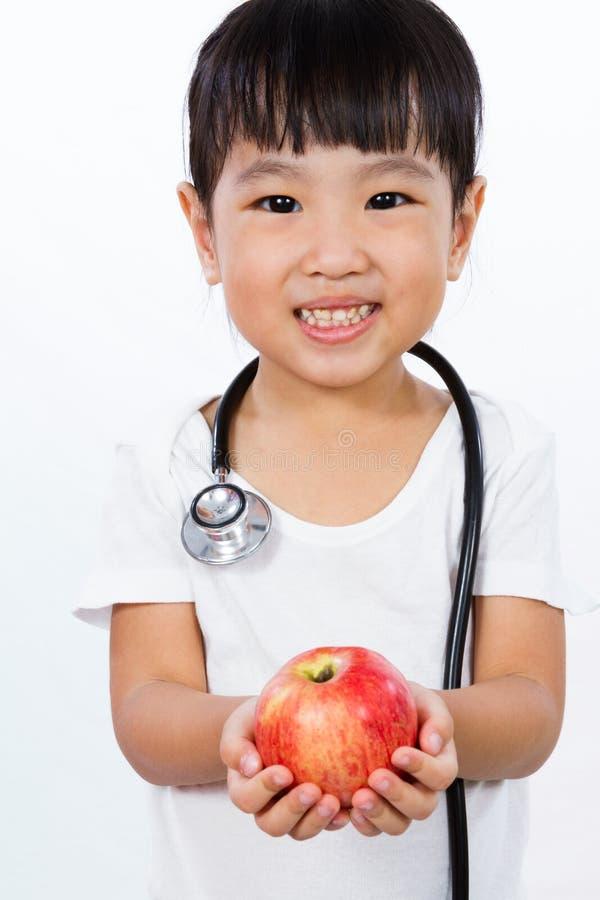 La piccola ragazza cinese asiatica si è agghindata come medico con uno Stethoscop fotografia stock