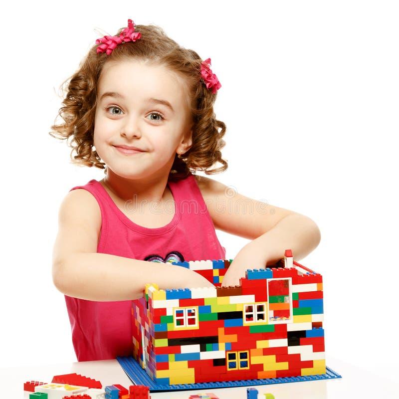 La piccola ragazza costruisce una casa dai blocchi di plastica fotografia stock libera da diritti
