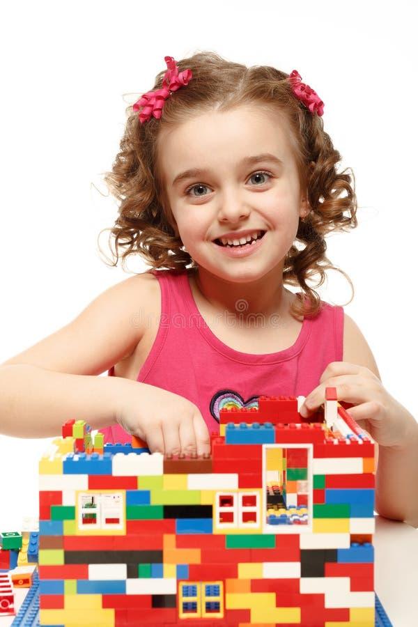 La piccola ragazza costruisce una casa dai blocchi di plastica immagini stock