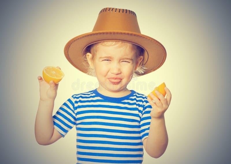 La piccola ragazza divertente tiene i limoni immagini stock