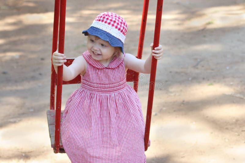 La piccola ragazza felice in cappello e vestito oscilla fotografie stock libere da diritti