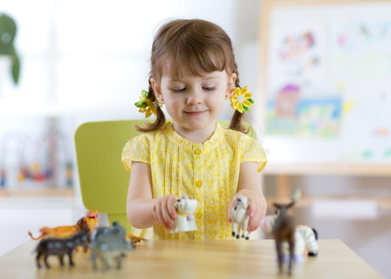 La piccola ragazza felice del bambino gioca lo zoo a casa o il centro di guardia immagini stock libere da diritti